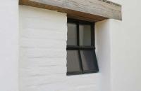 opstekend ijzer raam in een stenen muur