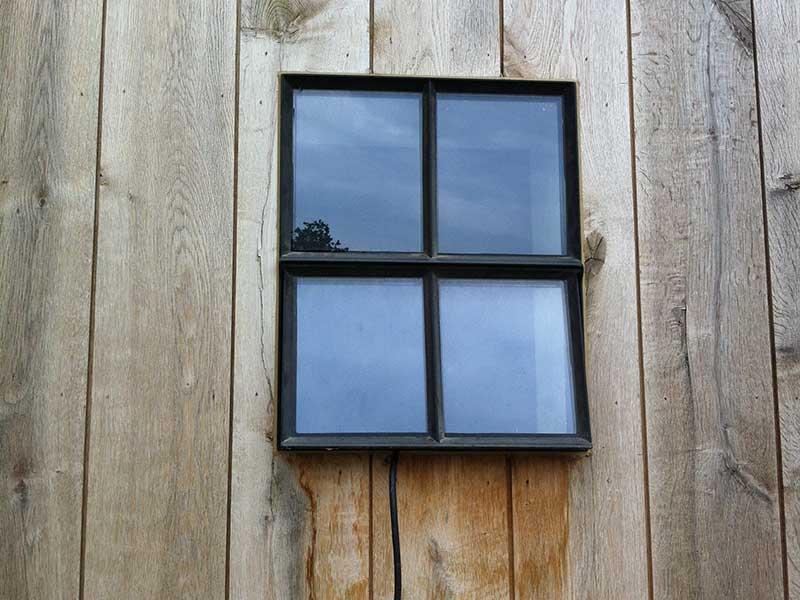 houten gevel - buitenhuis-tuinhuis-bijgebouw - gietijzeren raam - met opengaande klep